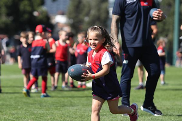 A girls running with the ball at a Demons Superclinic
