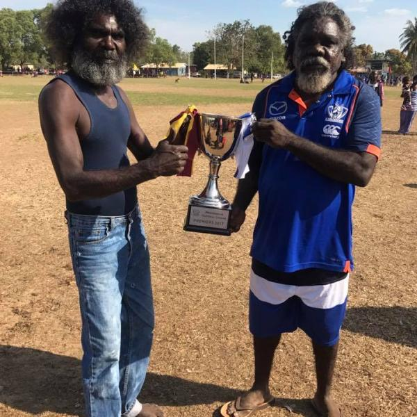 Lions and Malamalarra coach's holding the premiership cup before the Maningrida grand final