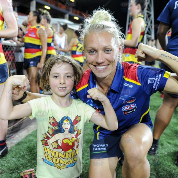 Erin Phillips showing off her guns with a young fan for a photo